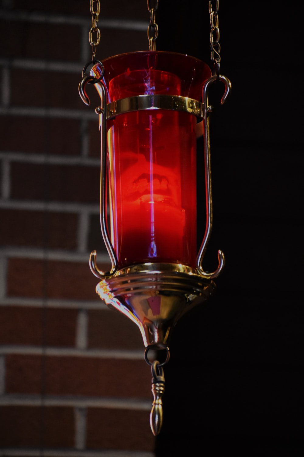 red and gold lamp near brown brick wall