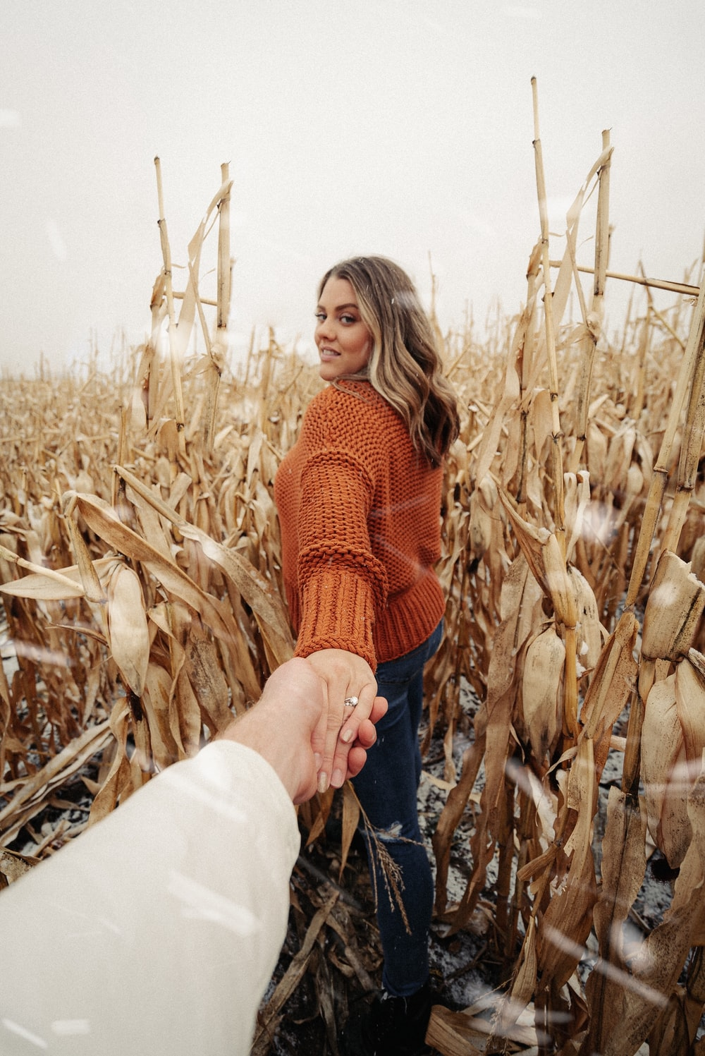 woman in red knit sweater and blue denim jeans standing on wheat field during daytime