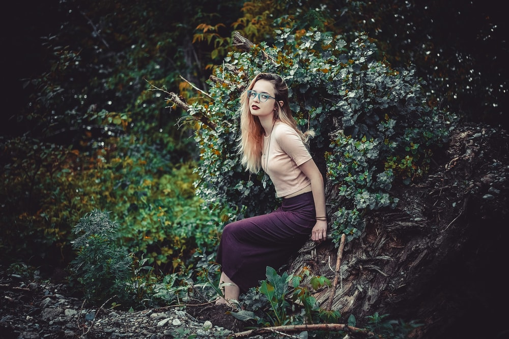 woman in brown long sleeve shirt and black pants sitting on ground surrounded by green plants