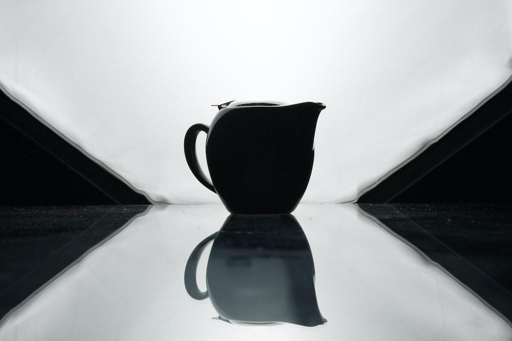 black ceramic teapot on white textile
