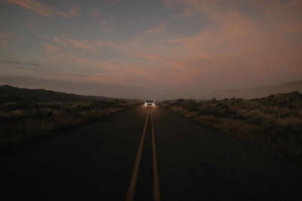 black asphalt road between green grass field during daytime