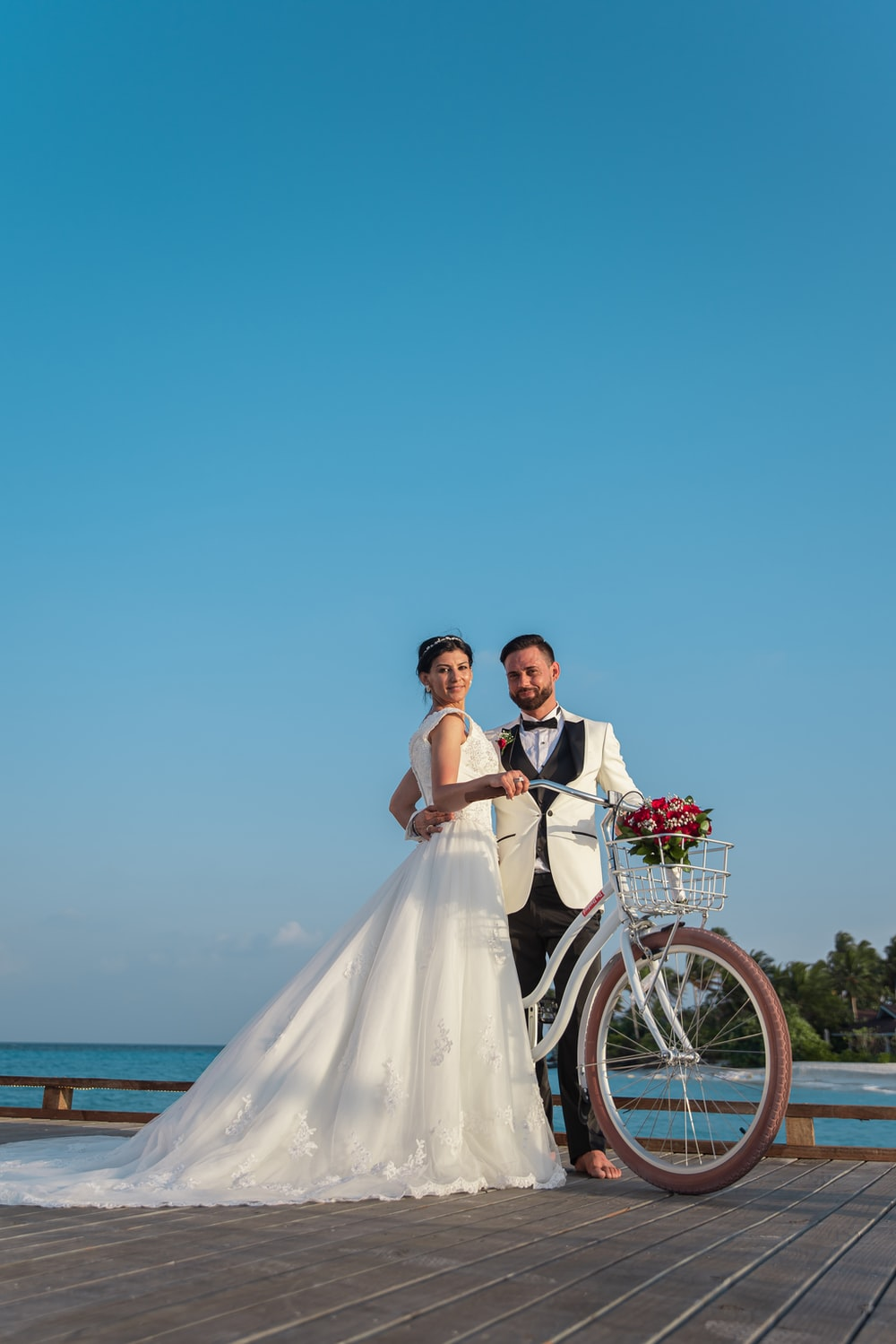 man and woman in wedding dress riding bicycle on beach during daytime