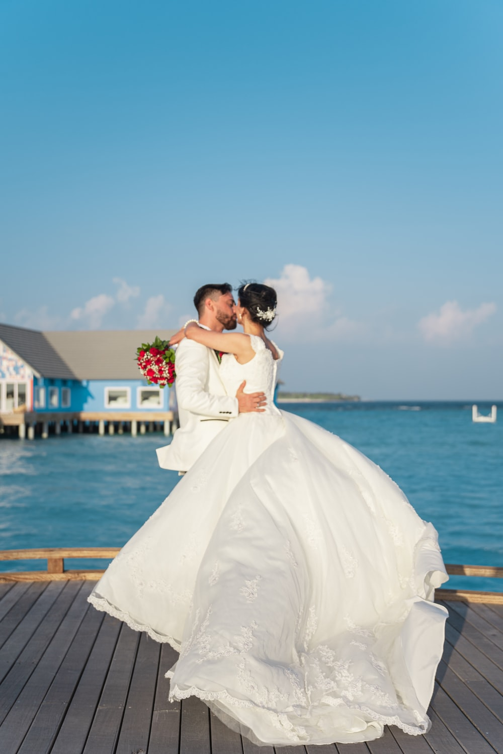 bride and groom kissing on dock during daytime