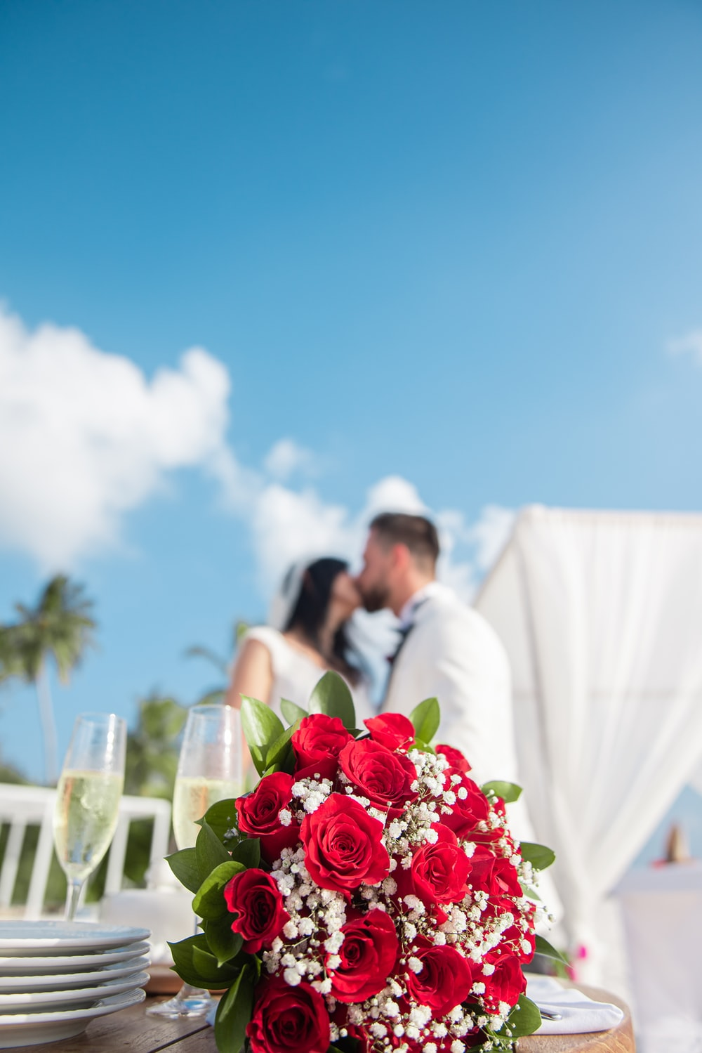 woman in white wedding gown holding bouquet of red roses