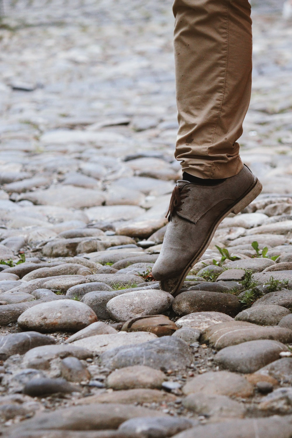 person in brown pants and brown boots standing on rocky ground during daytime