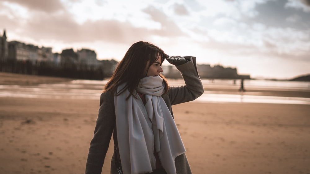 woman in white scarf standing on brown sand during daytime