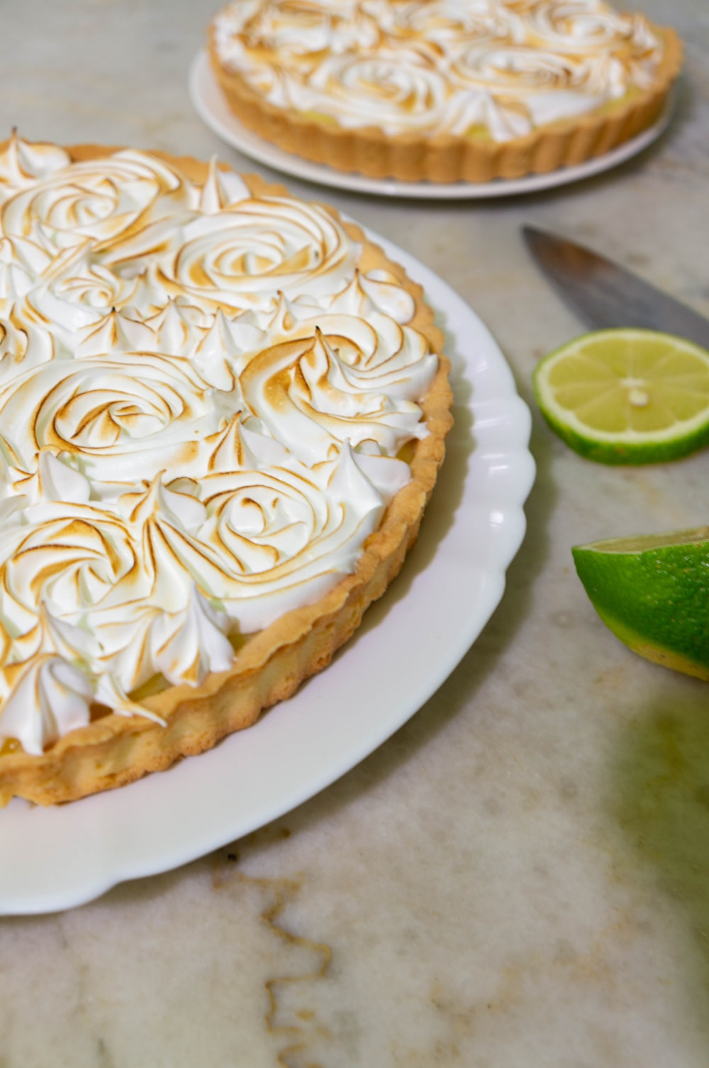 white icing cake with sliced of green citrus fruit on white ceramic plate