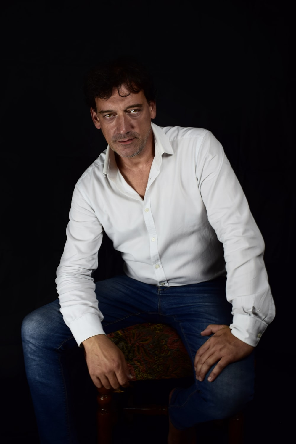man in white dress shirt and blue denim jeans sitting on brown wooden stool