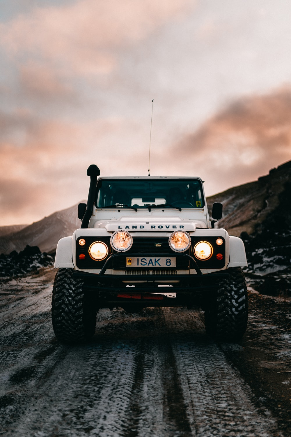 grayscale photo of black jeep wrangler on rocky hill