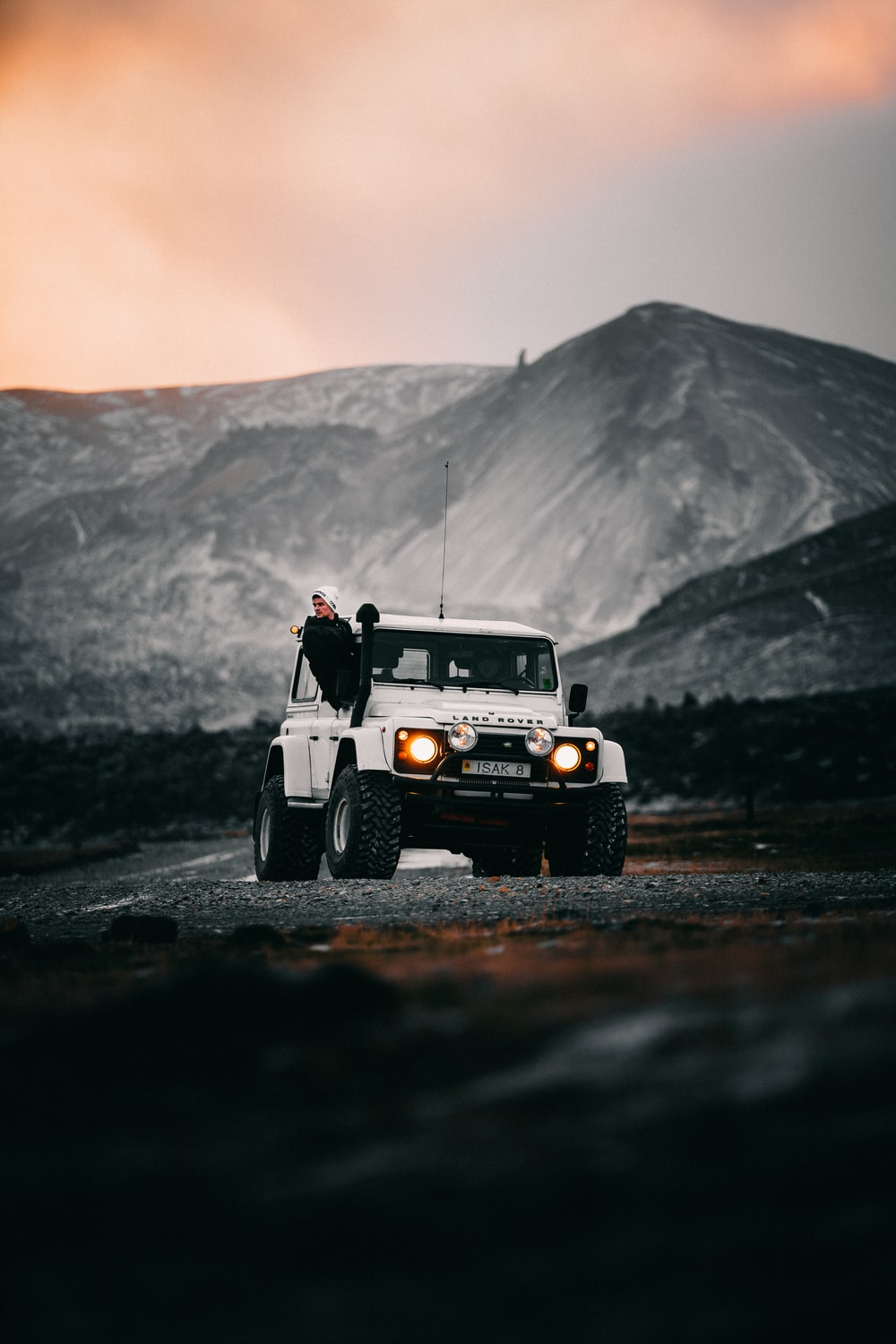 man in black jacket and pants standing beside white jeep wrangler on road during daytime