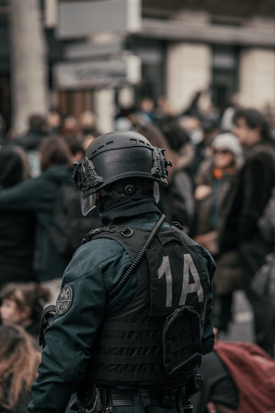Policeman standing in front of a crowd in Paris during the protests against Macron's gouvernement use of the law 49.3
