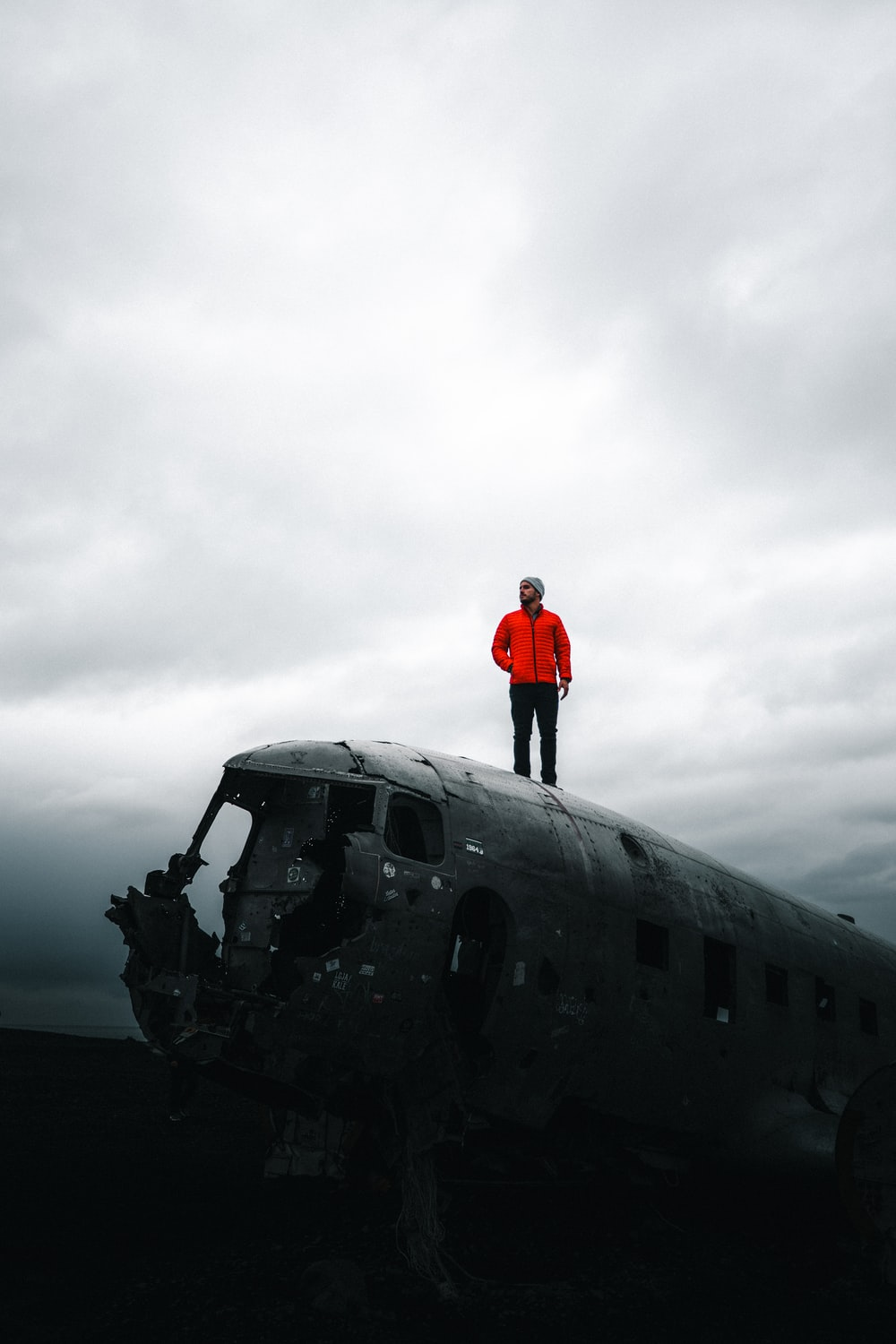 man in red jacket standing on black airplane under gray cloudy sky during daytime