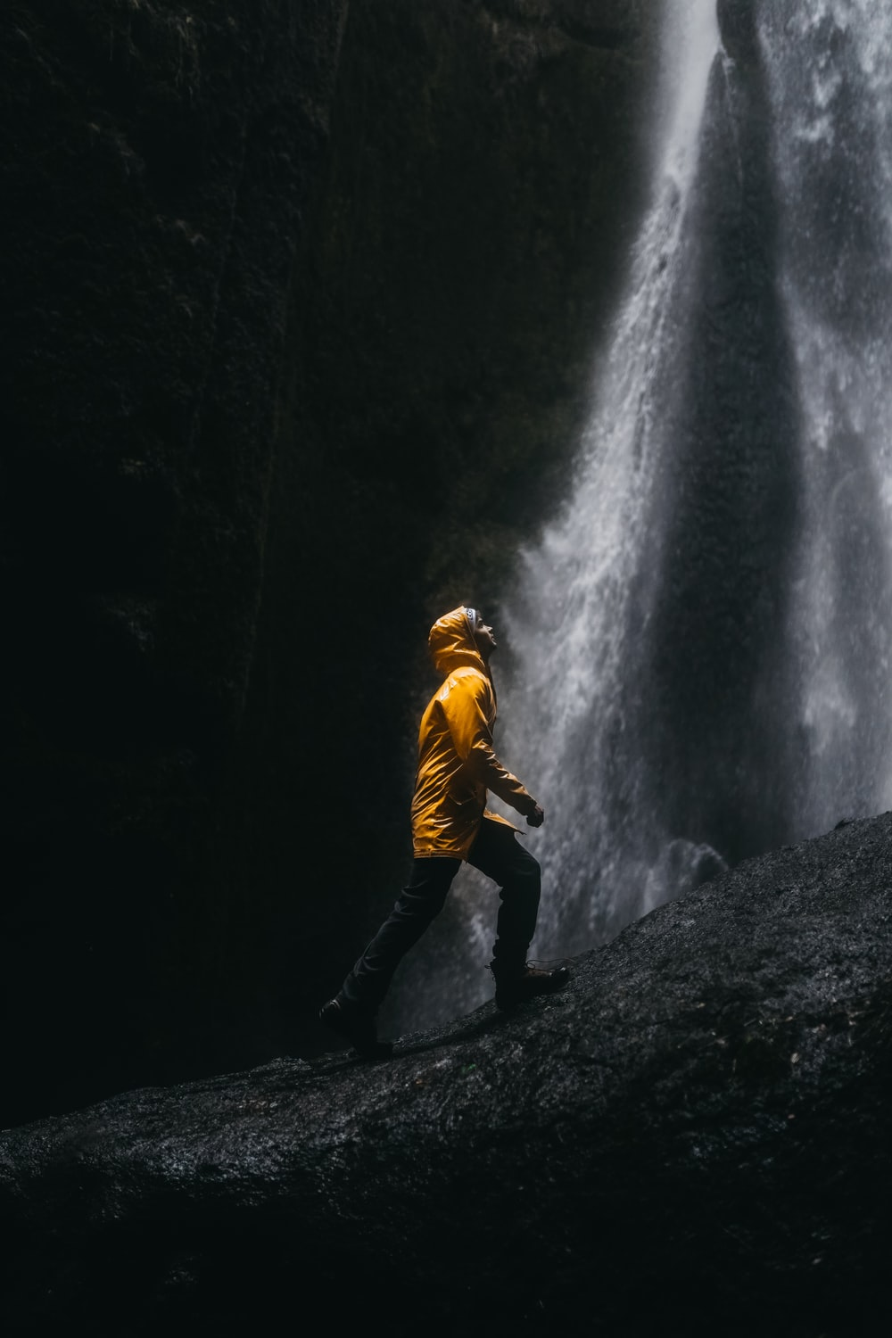 woman in yellow jacket and black pants standing on rock in front of waterfalls