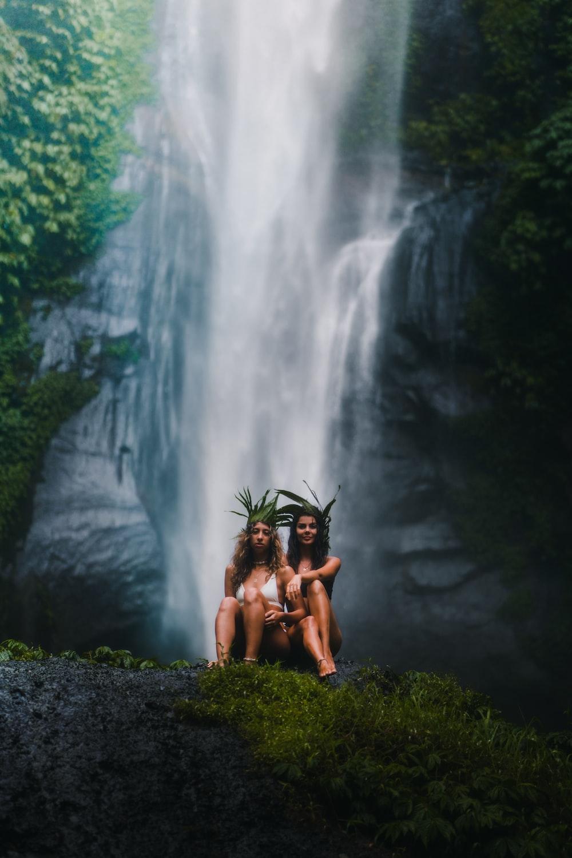 2 women sitting on rock near waterfalls during daytime
