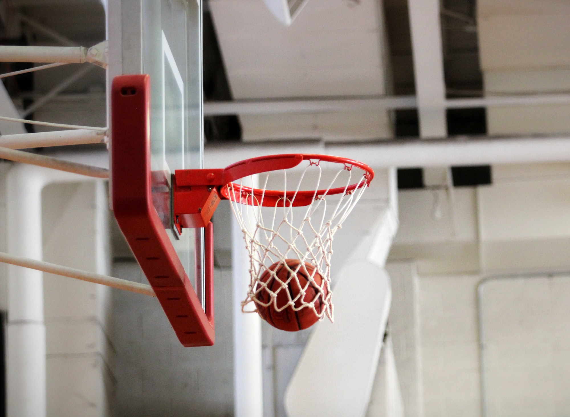 A basketball falls through the net of a basket.
