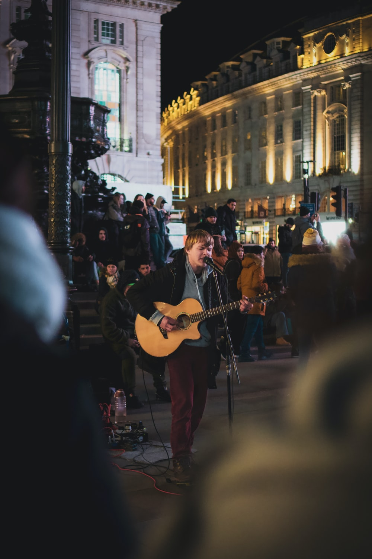 man in black t-shirt playing guitar on street during night time