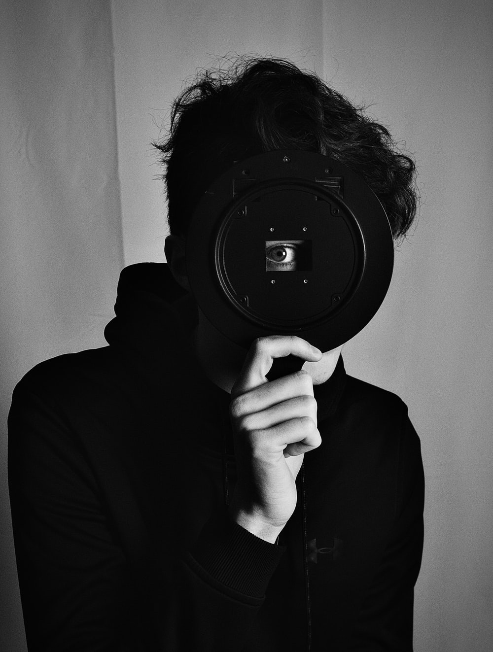 grayscale photo of person holding camera lens