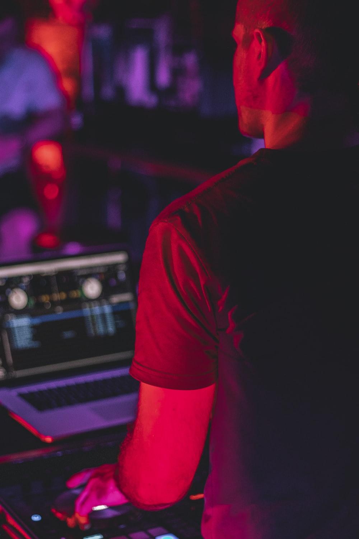 man in black t-shirt standing in front of dj mixer