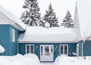 white wooden house on snow covered ground
