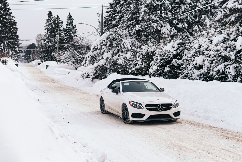 white mercedes benz coupe on snow covered road during daytime