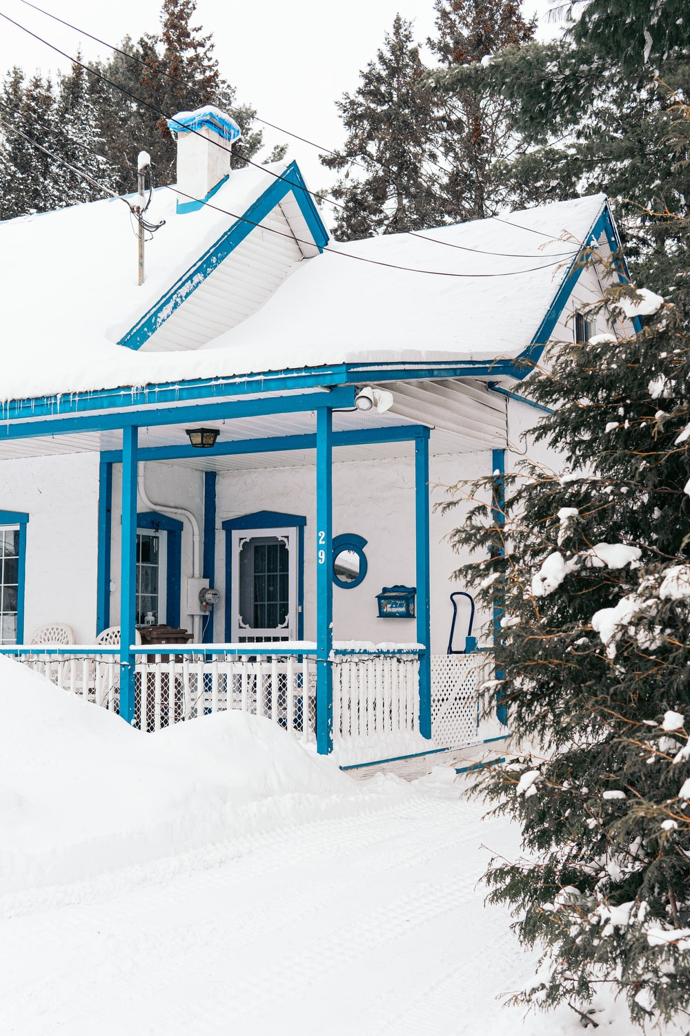 blue and white wooden house covered with snow