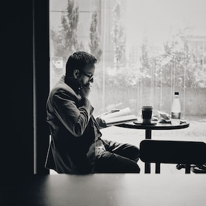 man in black jacket sitting by the table