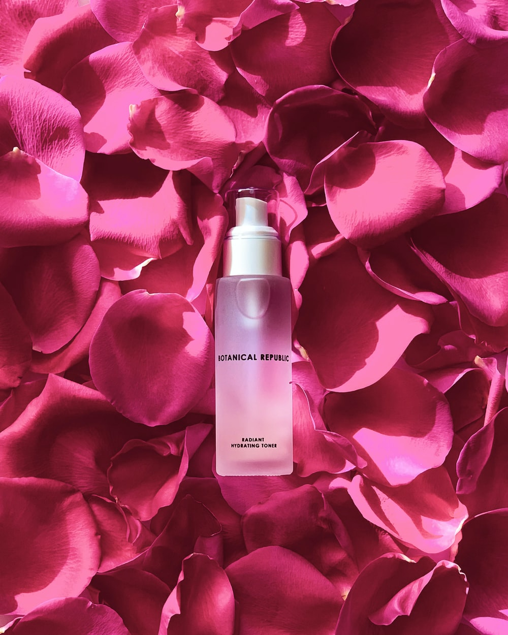pink and white perfume bottle on red rose