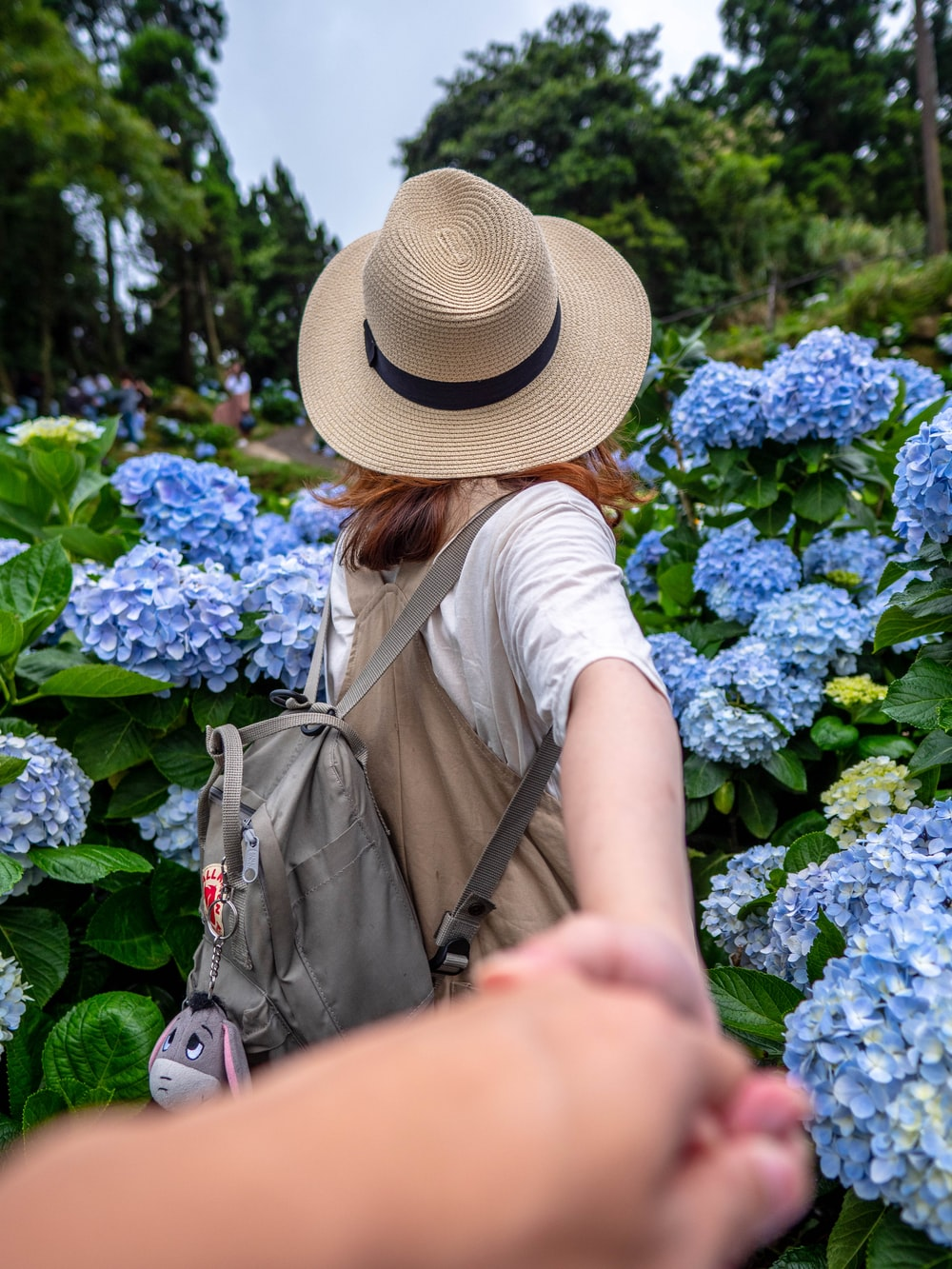 woman in white shirt and brown hat standing near blue flowers during daytime
