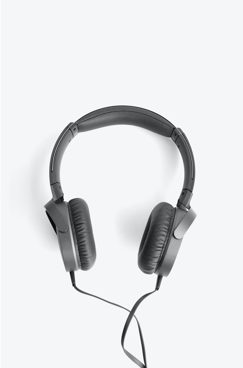 black and silver headphones on white surface