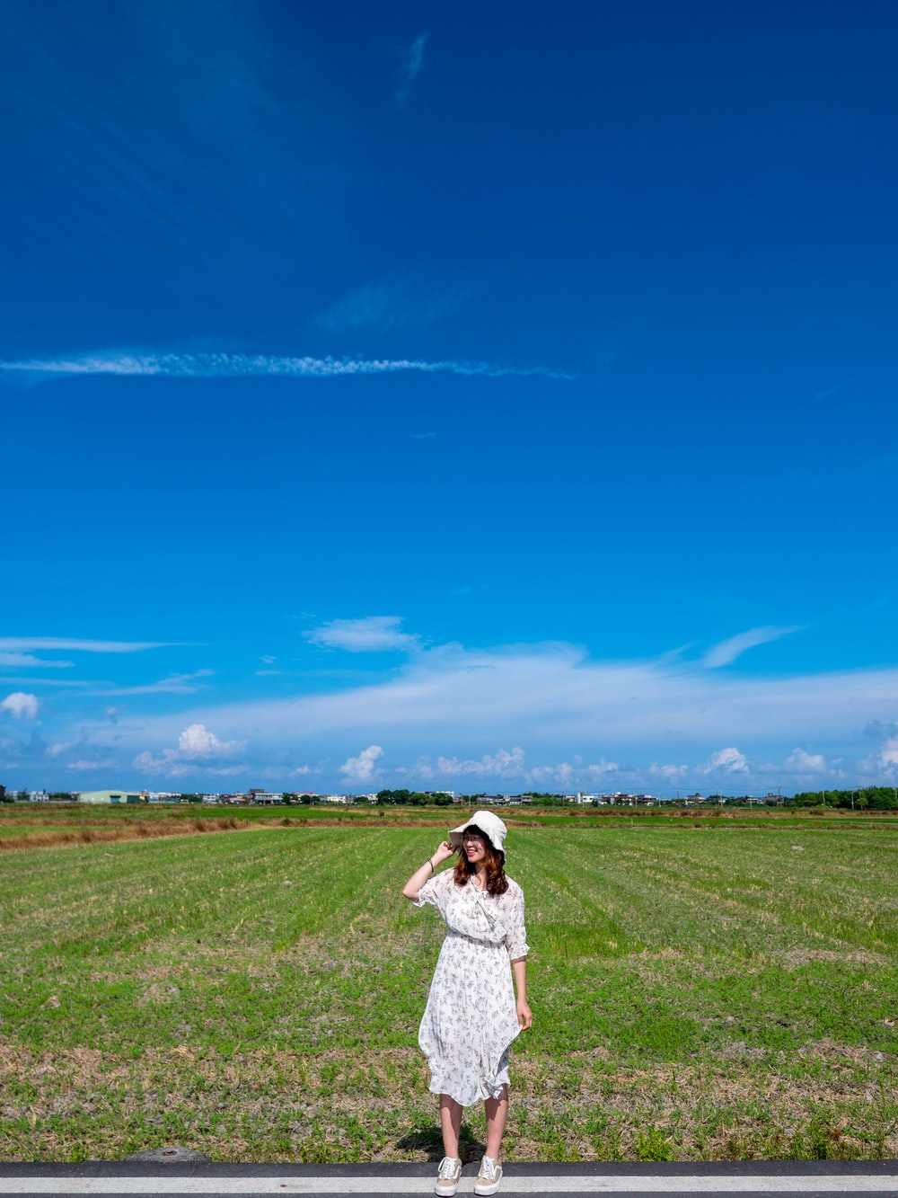 woman in white dress standing on green grass field under blue sky during daytime
