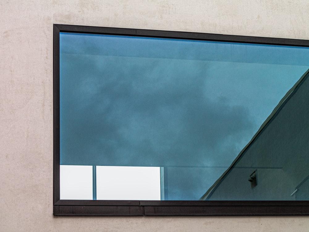 black framed glass window on gray concrete wall