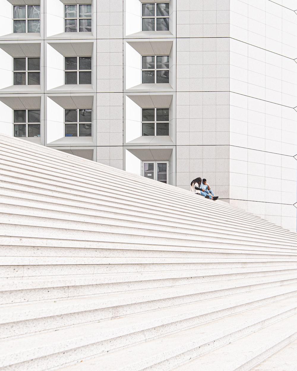 man in black jacket sitting on white concrete floor during daytime