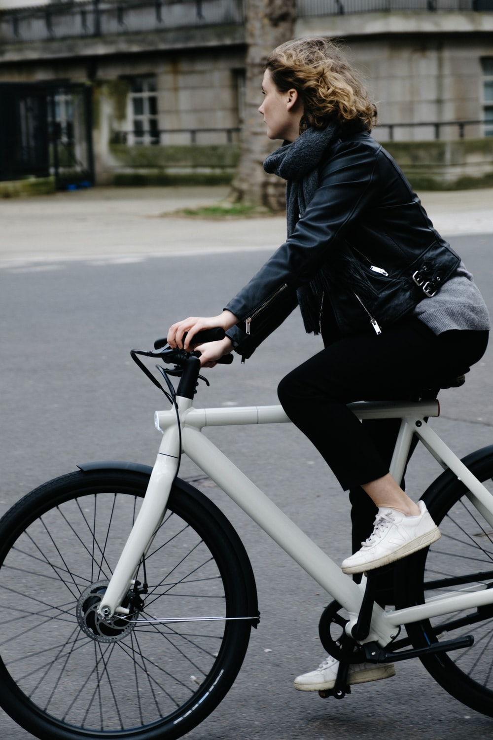 person in black jacket riding on white bicycle during daytime