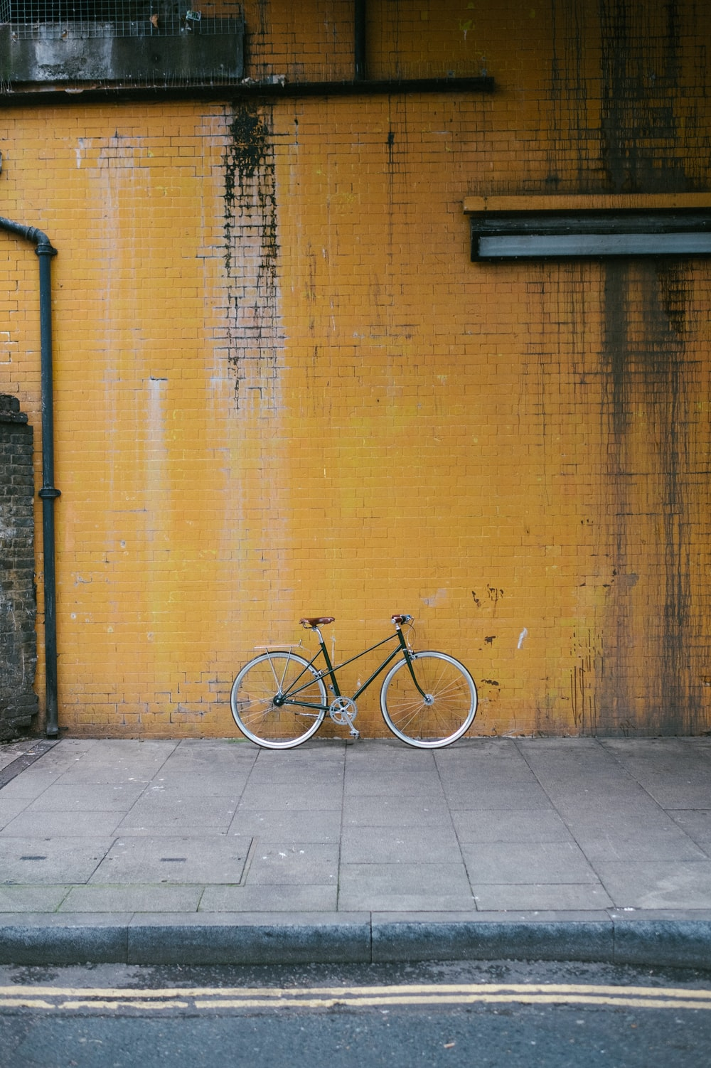 white city bike leaning on brown wall