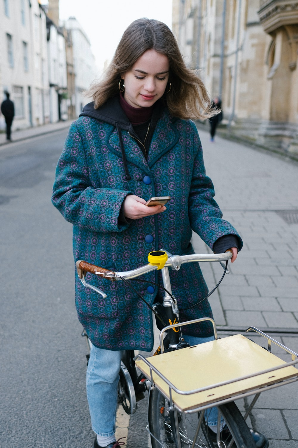 woman in red and black checkered coat and blue denim jeans holding yellow and black bicycle