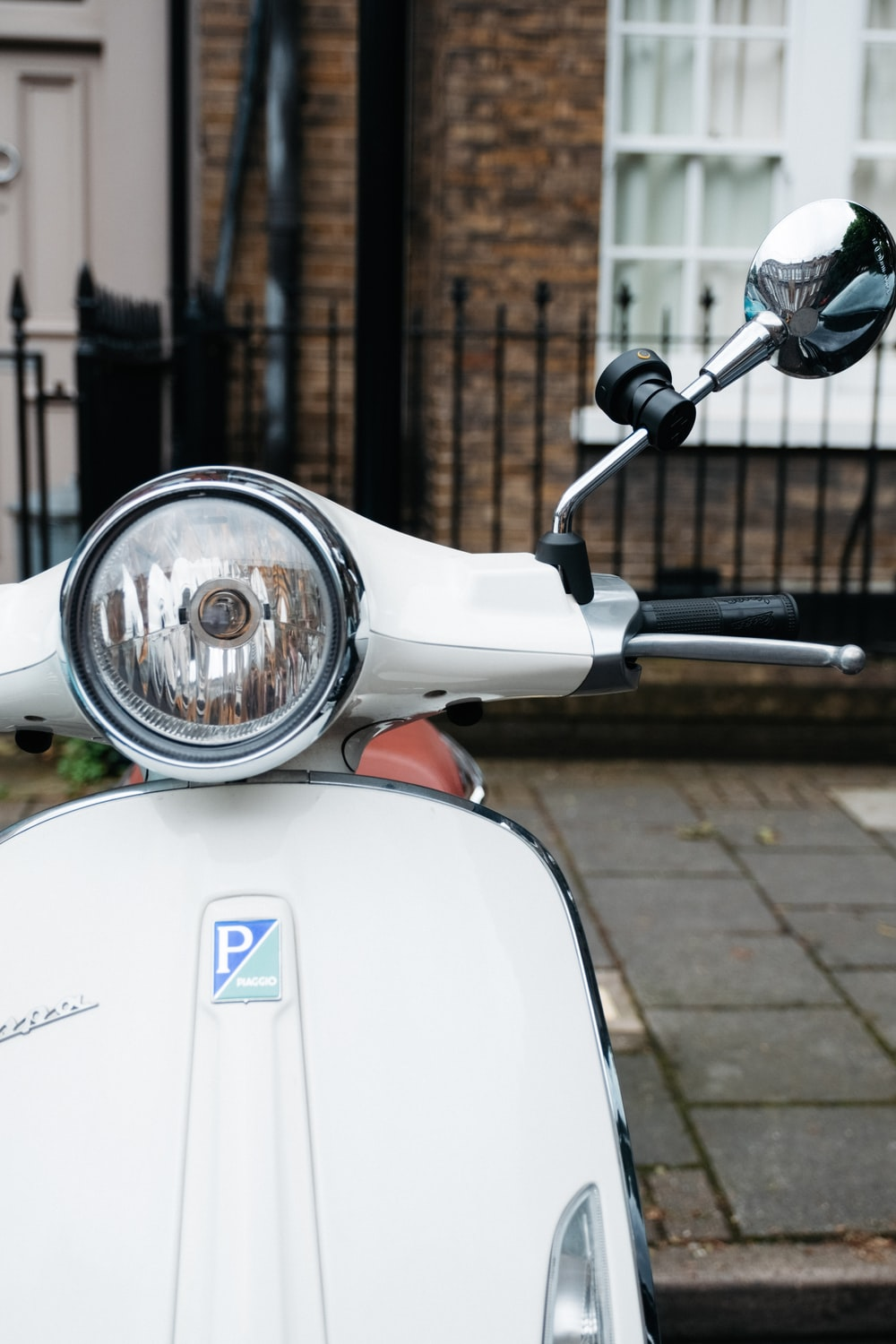 white and blue motor scooter parked beside brown brick wall