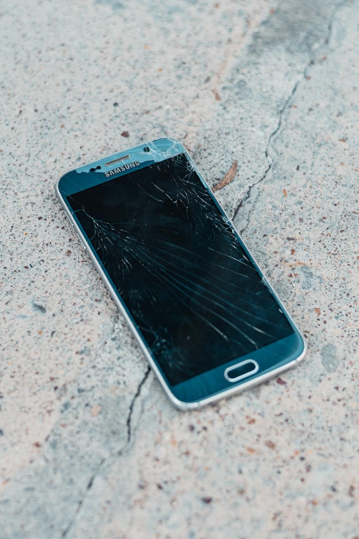 black samsung android smartphone on gray concrete floor