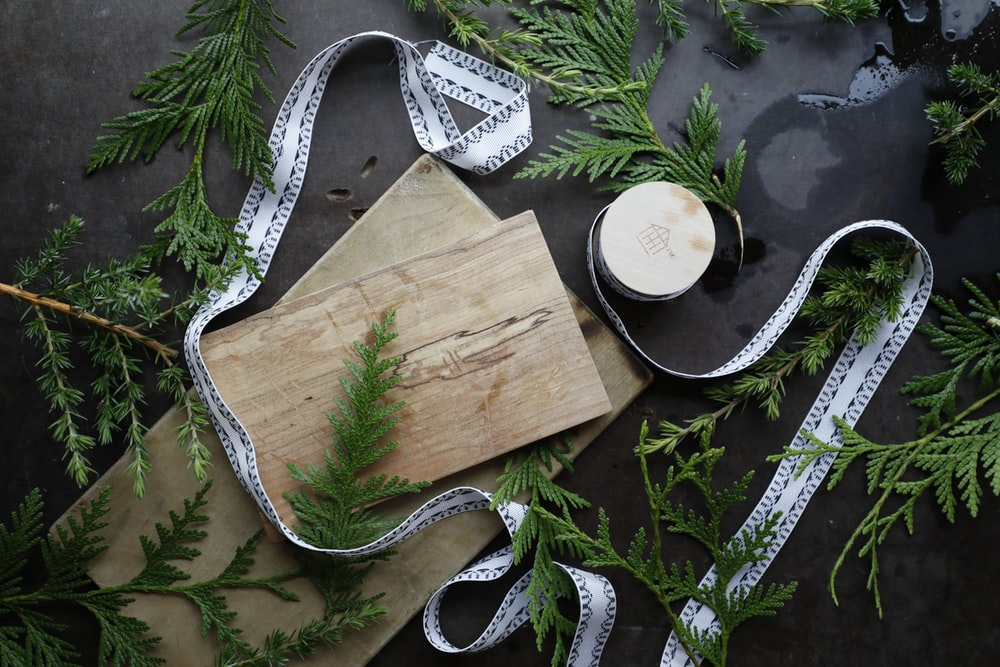 brown wooden chopping board on green leaves