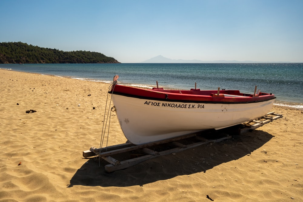 red and white boat on brown sand near body of water during daytime