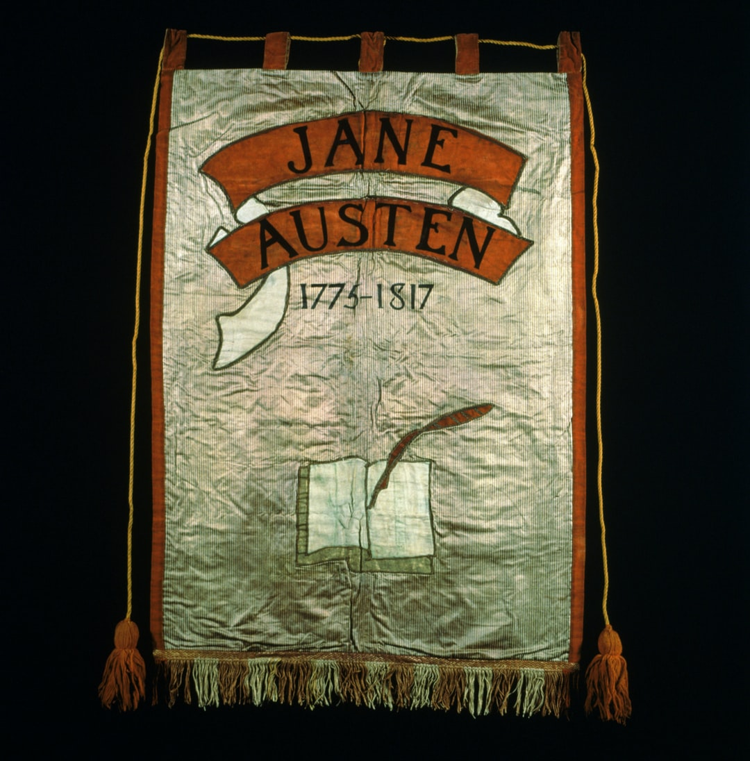 Jane Austen Suffrage Banner, 1908. Artist: Mary Lowndes. Cream yellow and red silk satin ground with black painted lettering and orange and cream appliqued scrolls and orange painted lettering. Cream wool book design. Yellow silk wrapped cords and orange tassels. F06DMAST