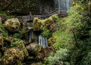 brown wooden bridge near waterfalls during daytime
