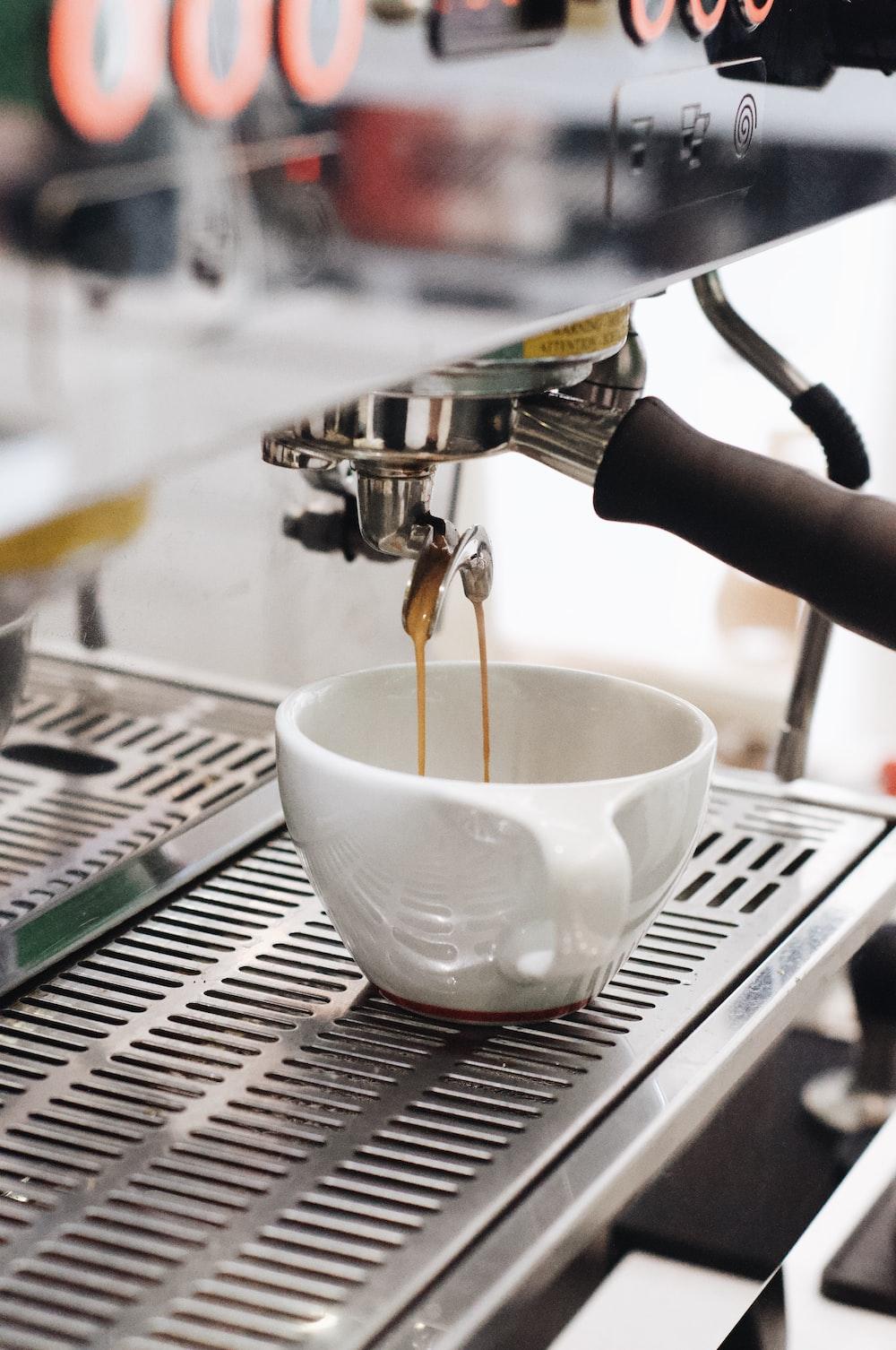 white ceramic cup on silver and black espresso machine