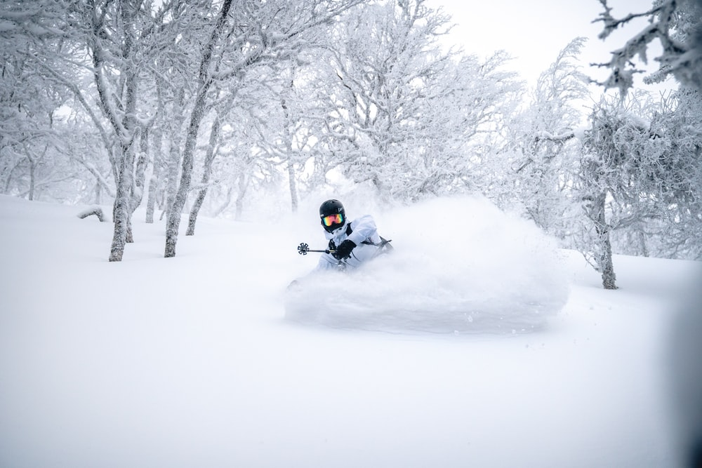 person riding on black motorcycle on snow covered ground during daytime