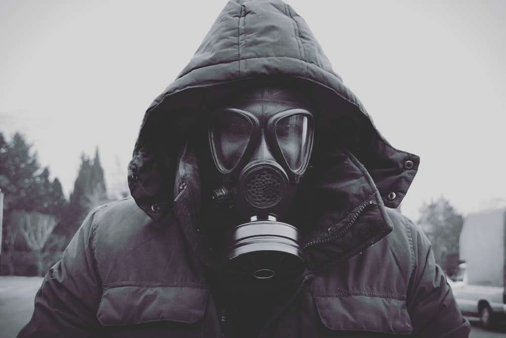 person wearing black leather jacket and gas mask