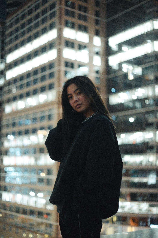 woman in black coat standing near glass window