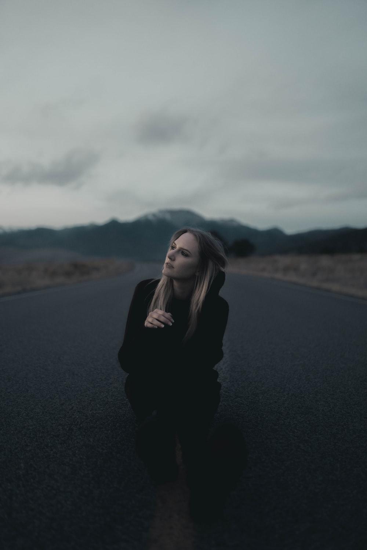 woman in black long sleeve shirt standing on black asphalt road during daytime