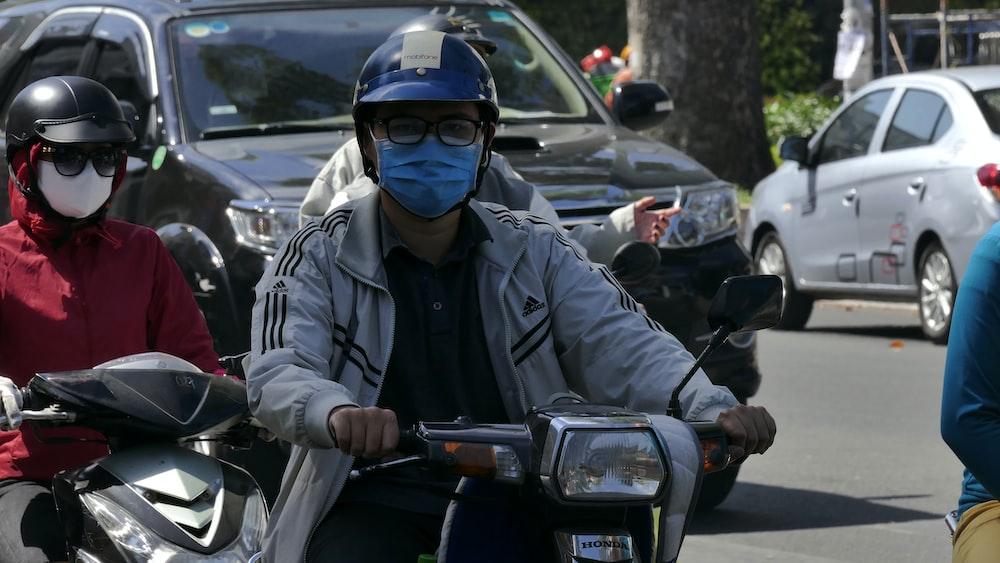 man in black jacket wearing blue helmet riding motorcycle during daytime