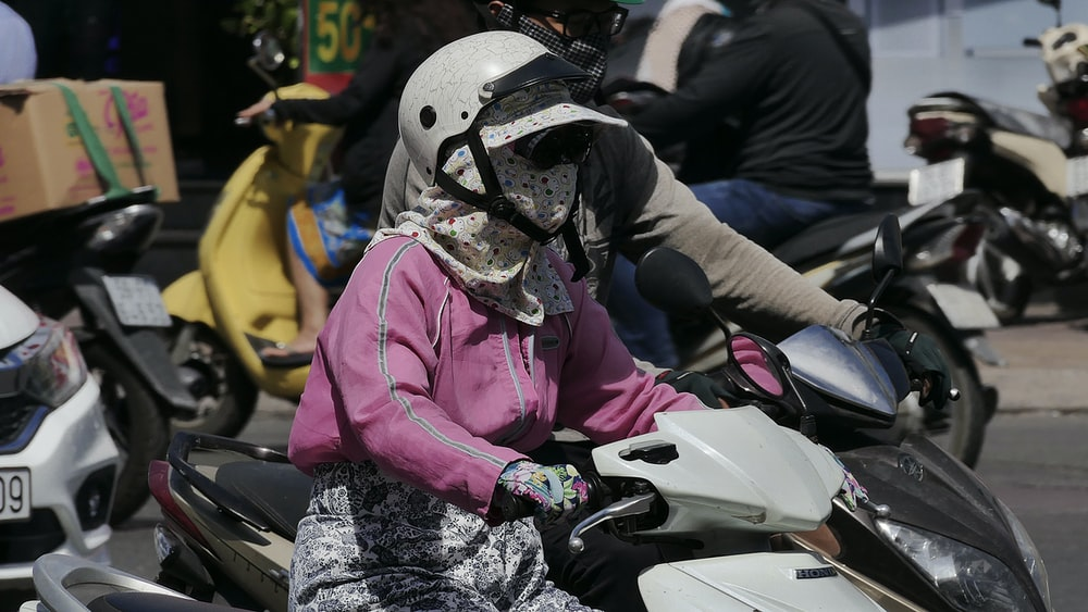 person in pink jacket wearing white helmet riding white and black motorcycle during daytime