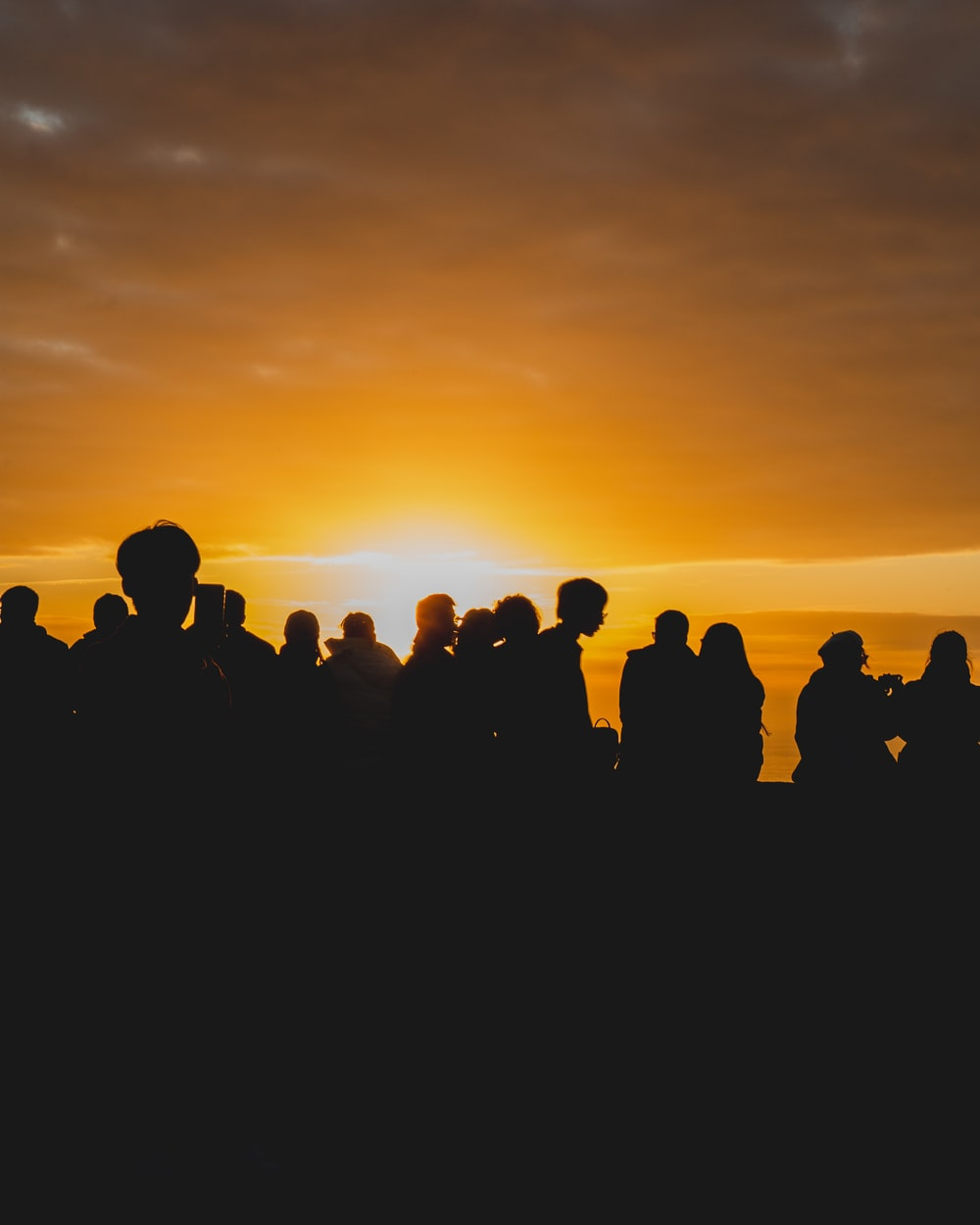 silhouette of people standing during sunset
