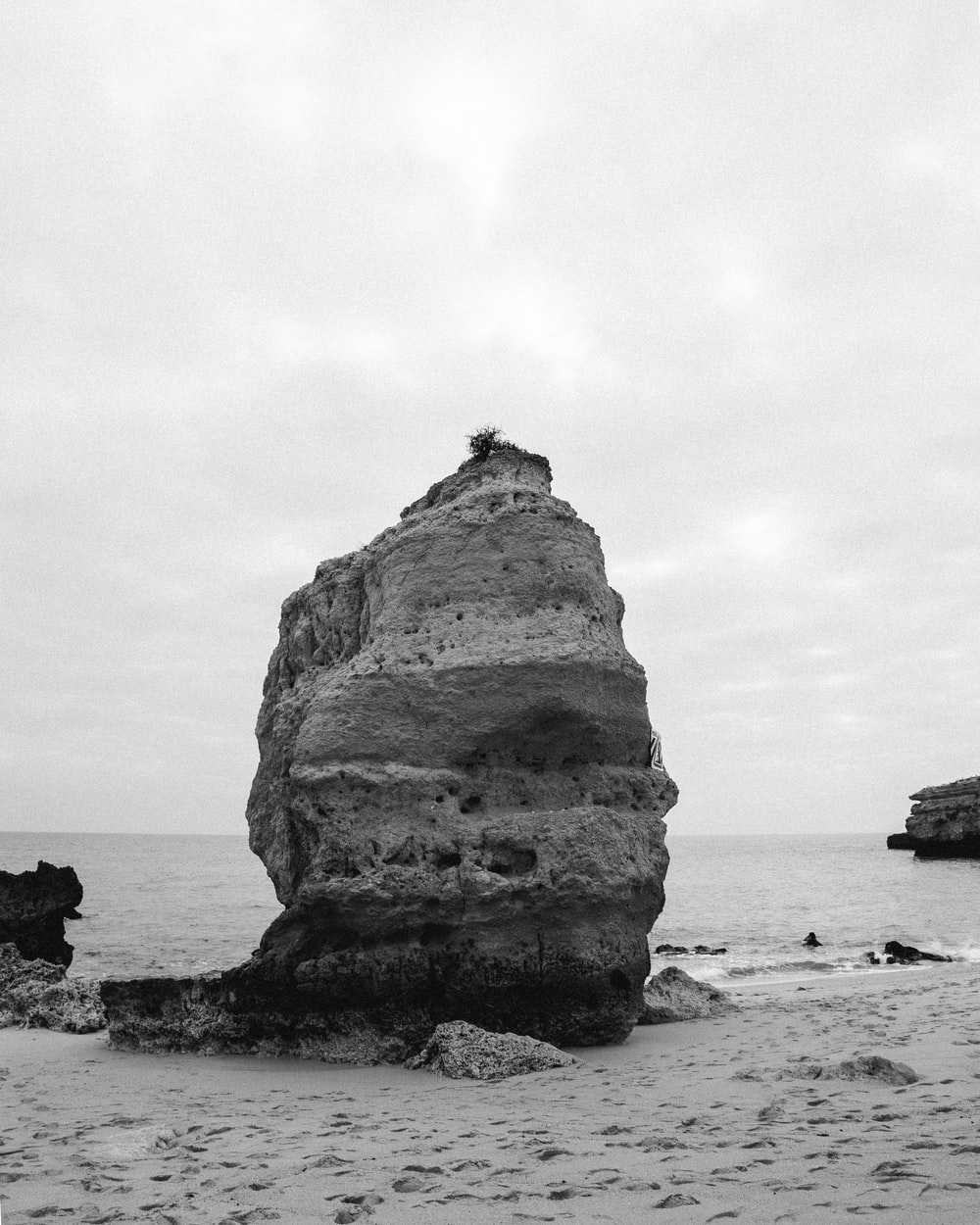 grayscale photo of rock formation on sea shore